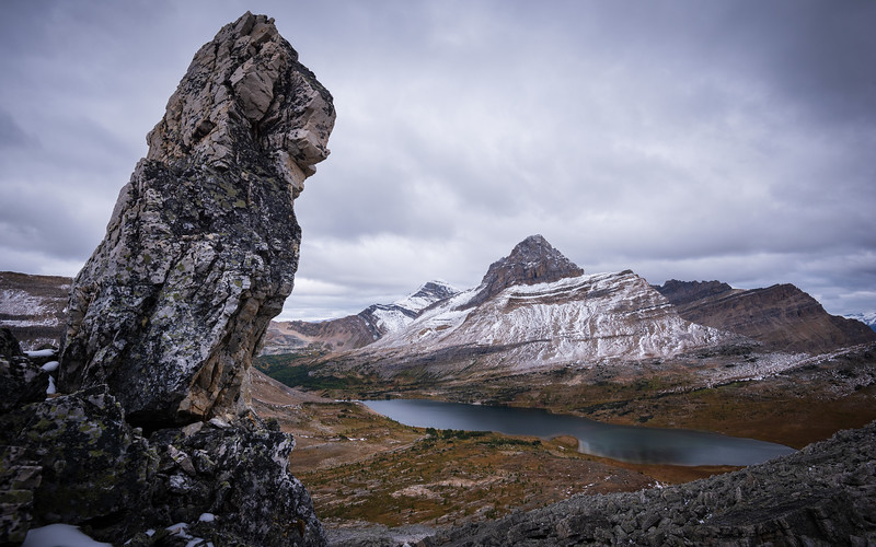 A large fin of rock that hasn't tumbled over. Ptarmigan mountain and lake in the background.