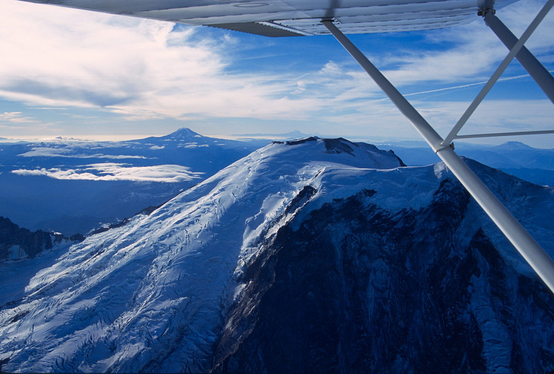 It took quite some time, but I managed to climb up to nearly 14,500 ft in the trusty C-120 for this shot of Mt. Rainier, looking south with Mt. Adams on the left, Mt. Hood just behind Rainier, and Mt. St. Helens between the struts on the right.