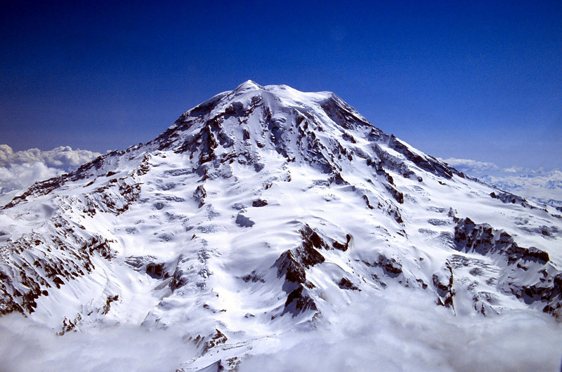 Mt. Rainier from the Southeast - the colors looking almost fake in this digitized slide photo. Very high contrast lighting conditions with clouds below and the bright white snow.