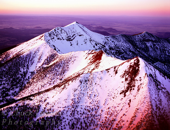 San Francisco Peaks; Flagstaff, AZ/April. Aerial view of the snow capped peaks at sunset. The cluster of mountains includes the highest elevation in Arizona, Humphrey's Peak at 12,633 ft.