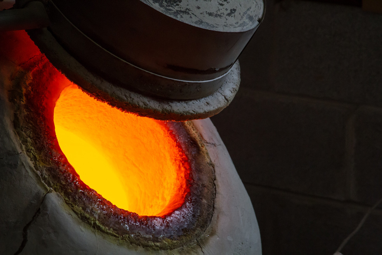 Hot Furnace with clear glass - he dips the blank rod in here first.
