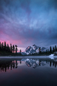 Early sunrise light breaks through a dramatic scene at Picture Lake, Washington