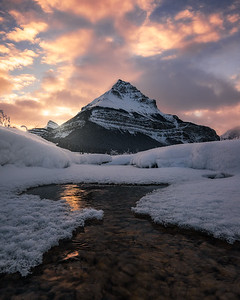 Tangle Peak and a partially frozen river during sunrise - Jasper National Park, Canada
