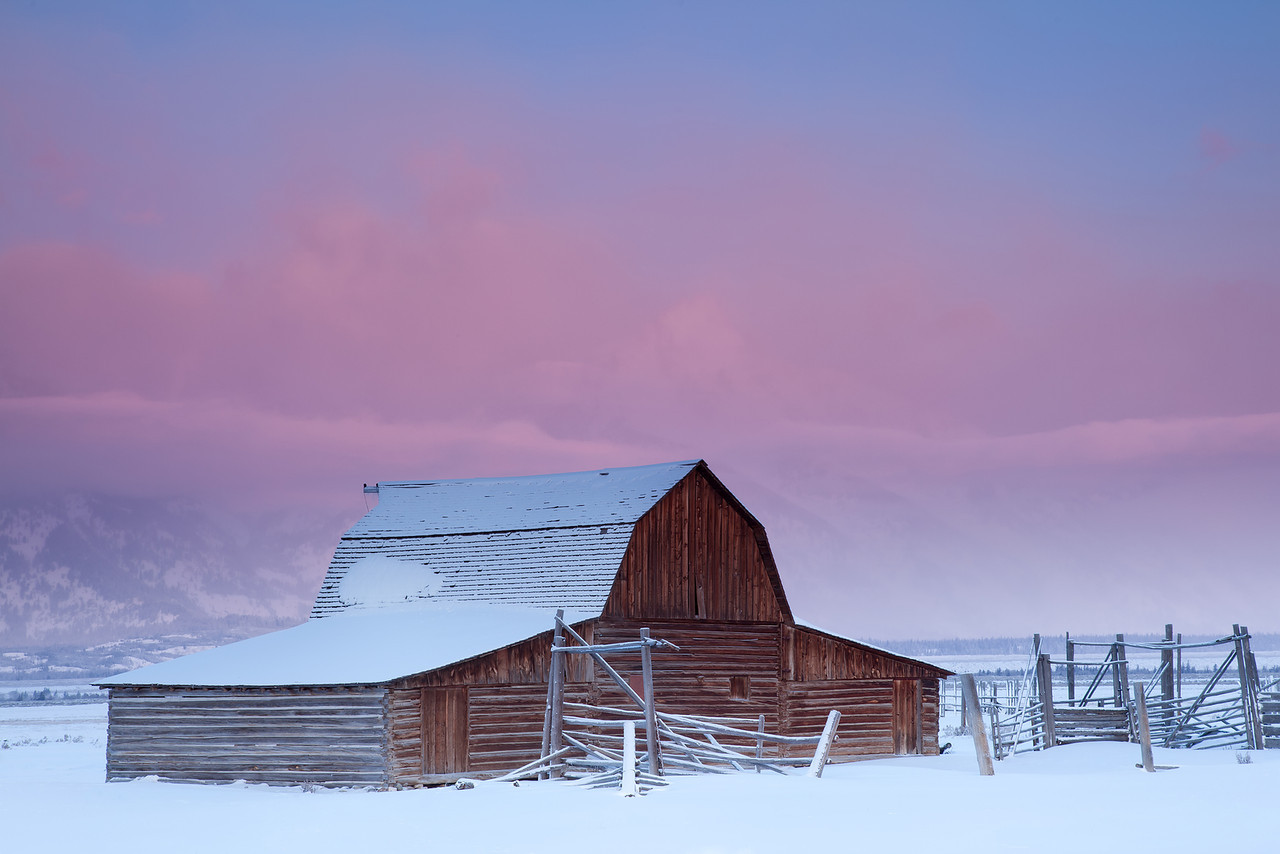 Frigid Sunrise - Soft pink light bathes the clouds covering the Tetons as the sun begins to rise to the east during a bitterly cold morning in Wyoming.
