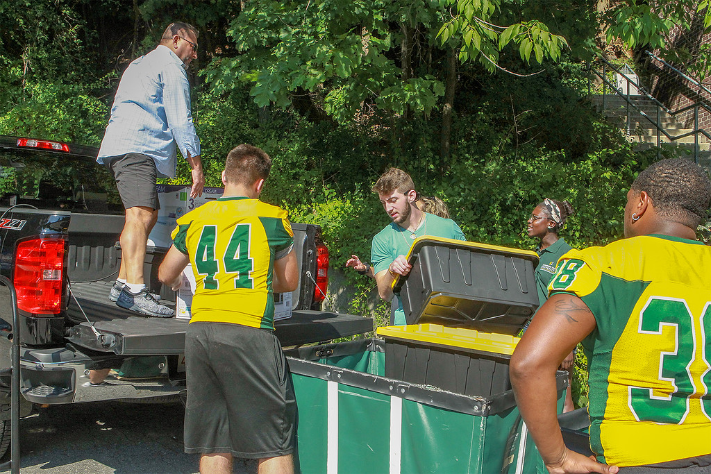 . MIchael Sellards from East Boston gets a hand from the football team unload family truck SENTINEL&ENTERPRISE/Scott LaPrade