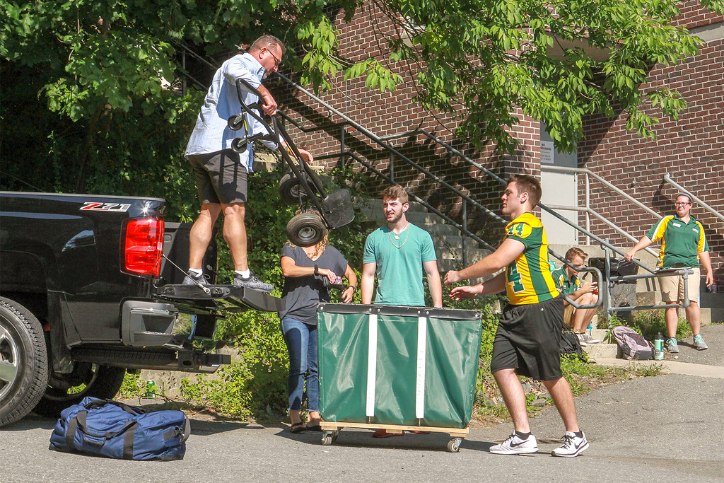 . Michael Sellards (middle ) from East Boston get\'s help from a football player unloading the family truck SENTINEL&ENTERPRISE/Scott LaPrade