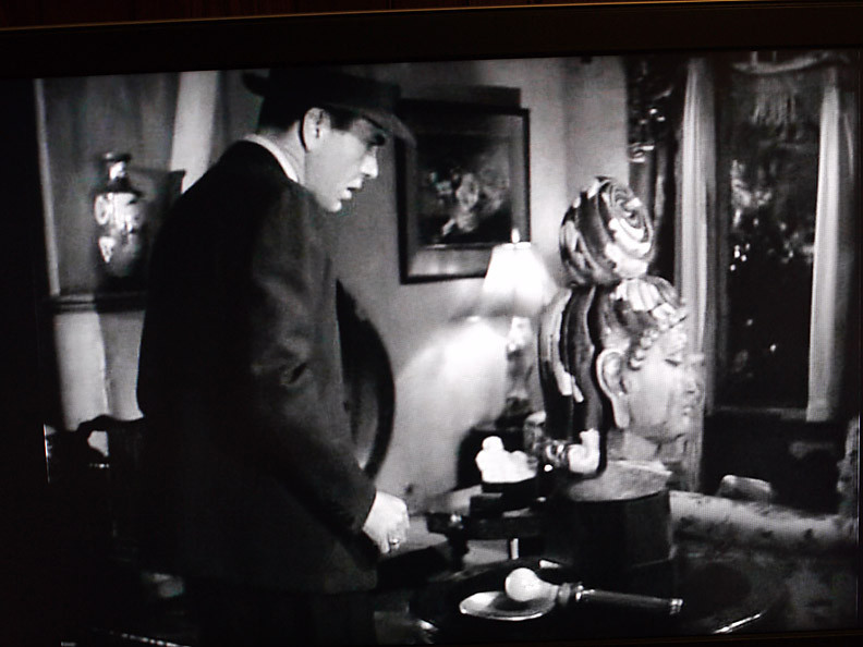 Marlowe checks out an art piece while investigating crime in The Big Sleep.
