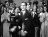Just as the photographer tries to take the photo a man, I believe it is Fredric March as a reporter, runs by and knocks the tripod and camera to the floor. In There Goes My Heart (1938).
