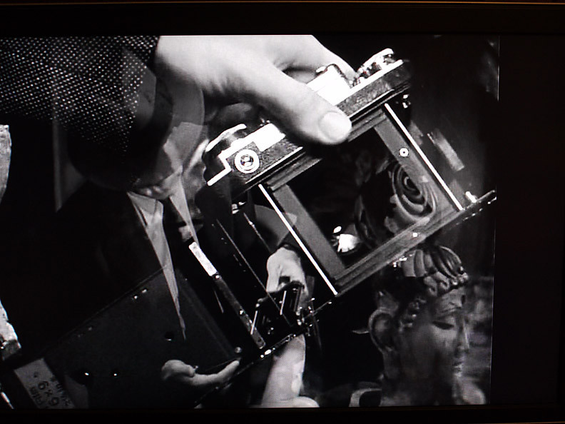 Marlowe takes the film out of the camera.