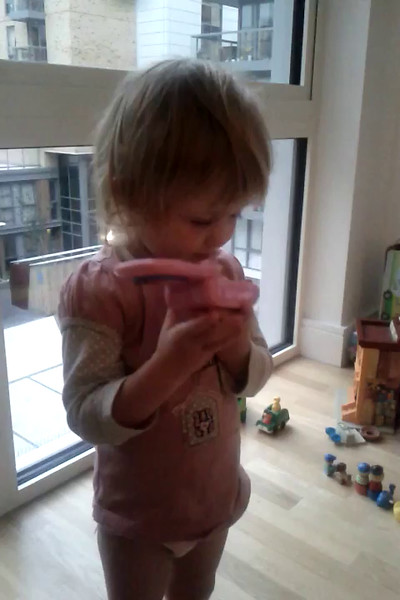Liri on the phone to Peppa. Just woke up from her nap, hence the shaggy hair and funny chatter!