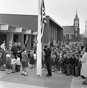 The flag is raised over St. Bernard's new elementary school as some 400 children look on. The flag-raising was one of the highlights of the April 5, 1965 event in which the children marched from their old building several blocks to the new building. Raising the flag is Kenneth Laudenschlager of the school's Home and Parents Group. (Times-Standard file photo)