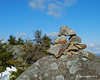 A cairn of small rocks on top of a large boulder