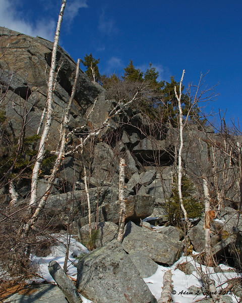 Boulders at the base of a small cliff next to the trail