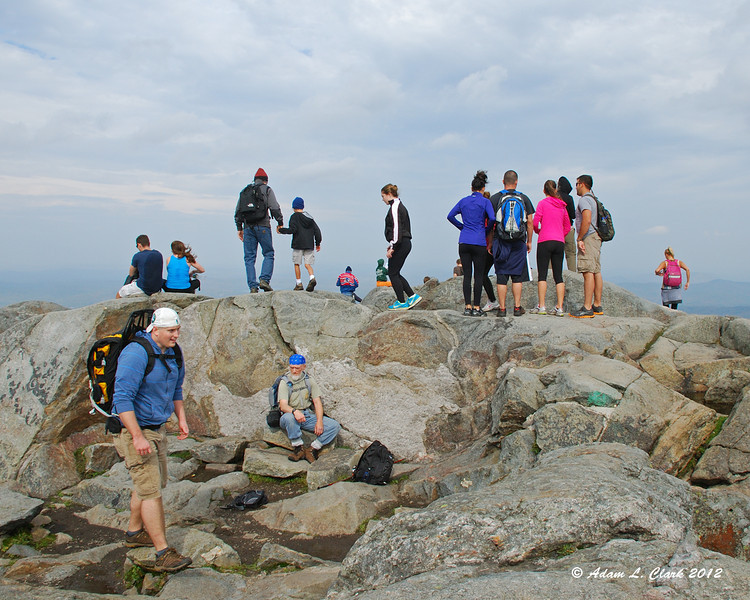 People walking about the summit, most before trying to find a spot out of the wind