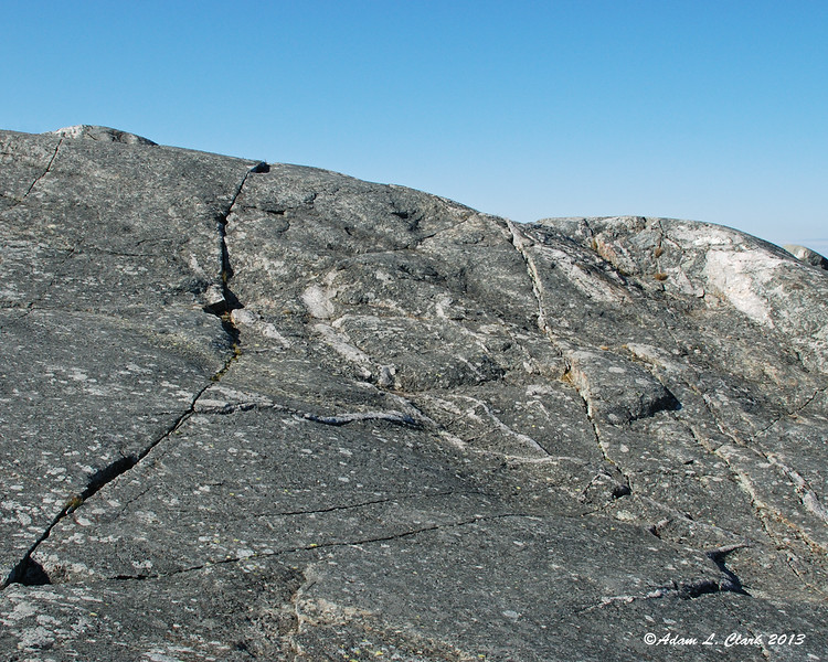 Cracks, lines, and varying minerals in the rock surface