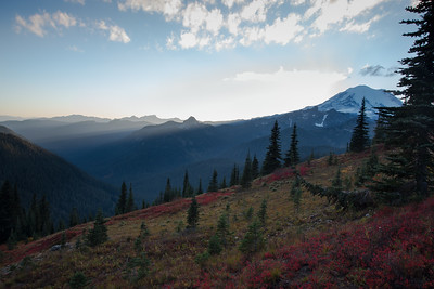 Light slices through the Cascade mountains, bending around Mt Rainier along the Naches Peak Loop trail in October