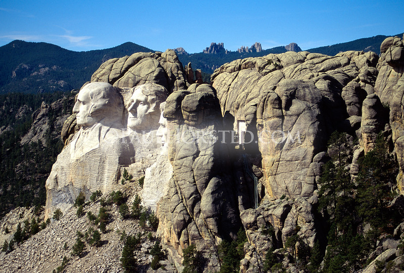 Aerial view of Mt. Rushmore, showing the carved presidential faces at left. The Hall of Records was carved into solid granite on the wall of the canyon behind the faces; the opening to the Hall of Records is visible in this view.