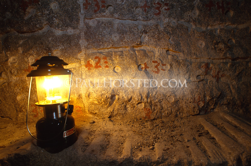 A lantern illuminates writing on the walls of the Hall of Records at Mt. Rushmore. The numbers were instructions written by sculptor Gutzon Borglum for his workers, telling them how much rock to drill or blast off in the next step of work. The Hall of Records project was abandoned in the 1930's to focus all work on finishing the faces on Mt. Rushmore.