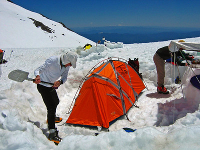 John Russell digs snow from around tent.