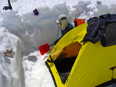 Jeff digs out the area around tent, and secures it from wind.