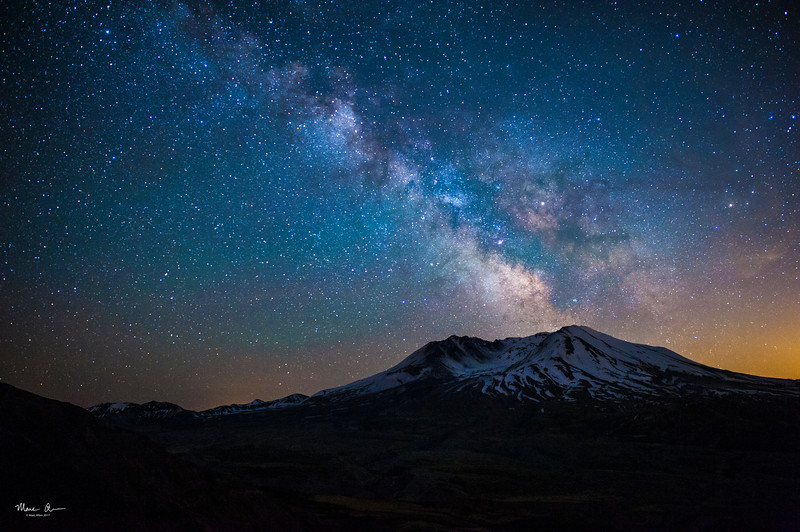 The Milky Way over Mt. St. Helens, as seen near the new moon on May 26, 2017.  The orange glow to the right is light pollution for Portland, Oregon.