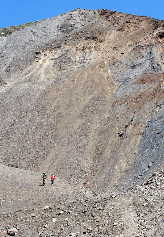 . Geotechnical engineers Ryan Turner and Jeff Scardine are dwarfed by the immense Mud Creek slide as they monitor continuing movement of the slide on Highway One south of Big Sur on Monday, May 7, 2018.  (Vern Fisher - Monterey Herald)