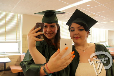 Cristina Marconcini and Sydney Martin maneuver a selfie-swap prior to Dennis-Yarmouth Regional High School commencement exercises Saturday. . .