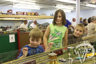 Model train club displays collectors' gems,  PAGE 15RAIL TRAIL Zachary Brennan, 4, of Deerfield; Anabelle, 8, and Max 10, Mandel from Reno, Nev., await a model train at Nauset Model Railroad Club's display in Orleans.  Cape Cod Day  AUGUST 16, 2011 front cover