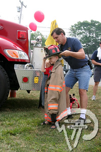 Safety firstBrennan McLoughlin of Brewster tries on the gear worn by firefighterKirk Riker of the Brewster Fire Department, at Public Safety Daylast Saturday at Drummer Boy Park. The Cape Codder JULY 25, 2008page 24