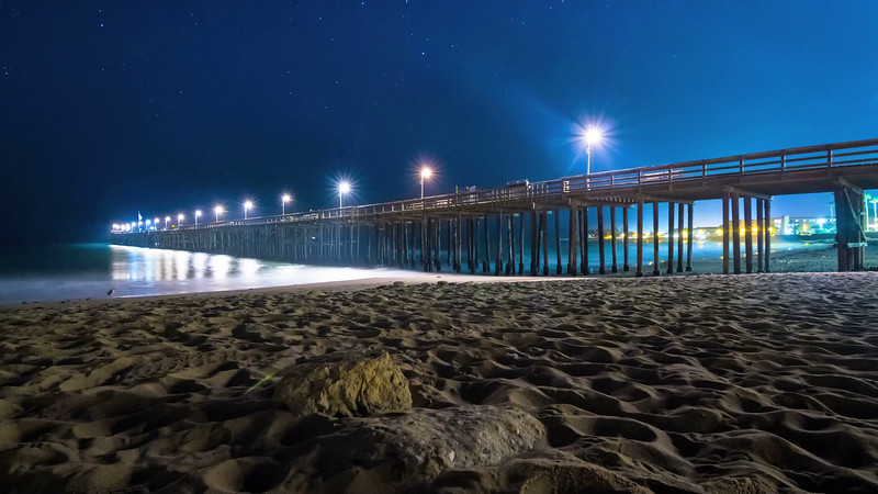 Beach time lapse with stars drifting over Ventura Pier