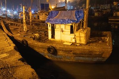 Before sunrise exploration of the chaotic docks. Sodium vapor lamps light the scene.