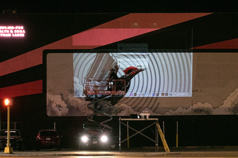 Local Fitchburg artist Jon Allen works on his fourth mural for the city on the back of the Putnam Bowling alley's building that faces Boulder Drive. He is painting a Pileated woodpecker hanging onto a microphone. He was working late on Friday night so he could use a projector to shine his image on the wall and paint over it. SENTINEL & ENTERPRISE/JOHN LOVE