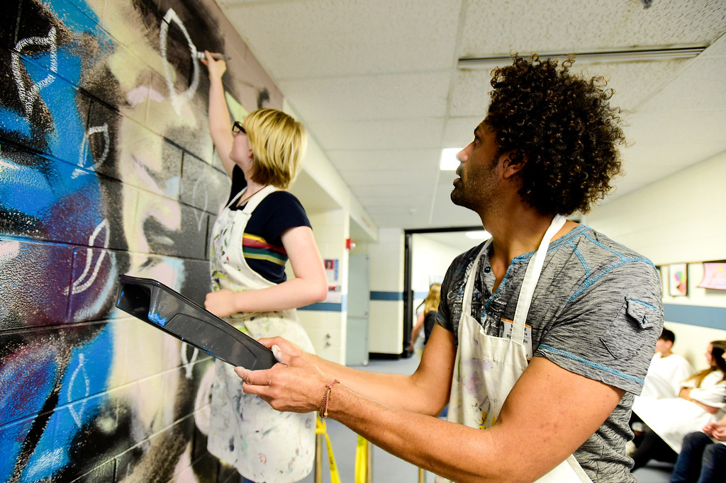 . BROOMFIELD, CO - APRIL 8:Artist Michael Gadlin works works with eighth grader Ingrid Quist, left, on a mural at Westlake Middle School in Broomfield on April 8, 2019. Gadlin is working with students to paint a 34-foot-long mural inside the school. (Photo by Matthew Jonas/Staff Photographer)