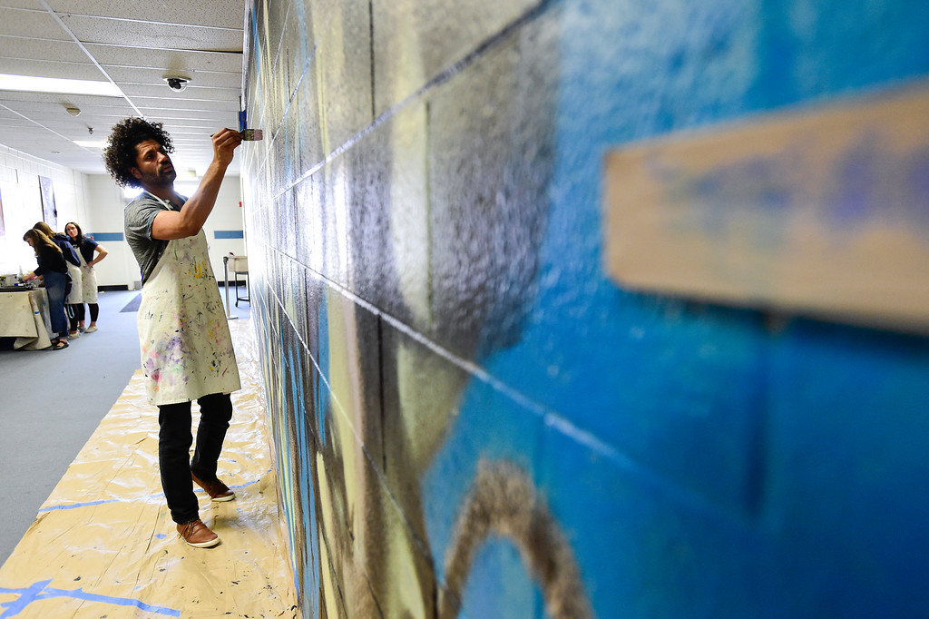 . BROOMFIELD, CO - APRIL 8:Artist Michael Gadlin works on a mural at Westlake Middle School in Broomfield on April 8, 2019. Gadlin is working with students to paint a 34-foot-long mural inside the school. (Photo by Matthew Jonas/Staff Photographer)