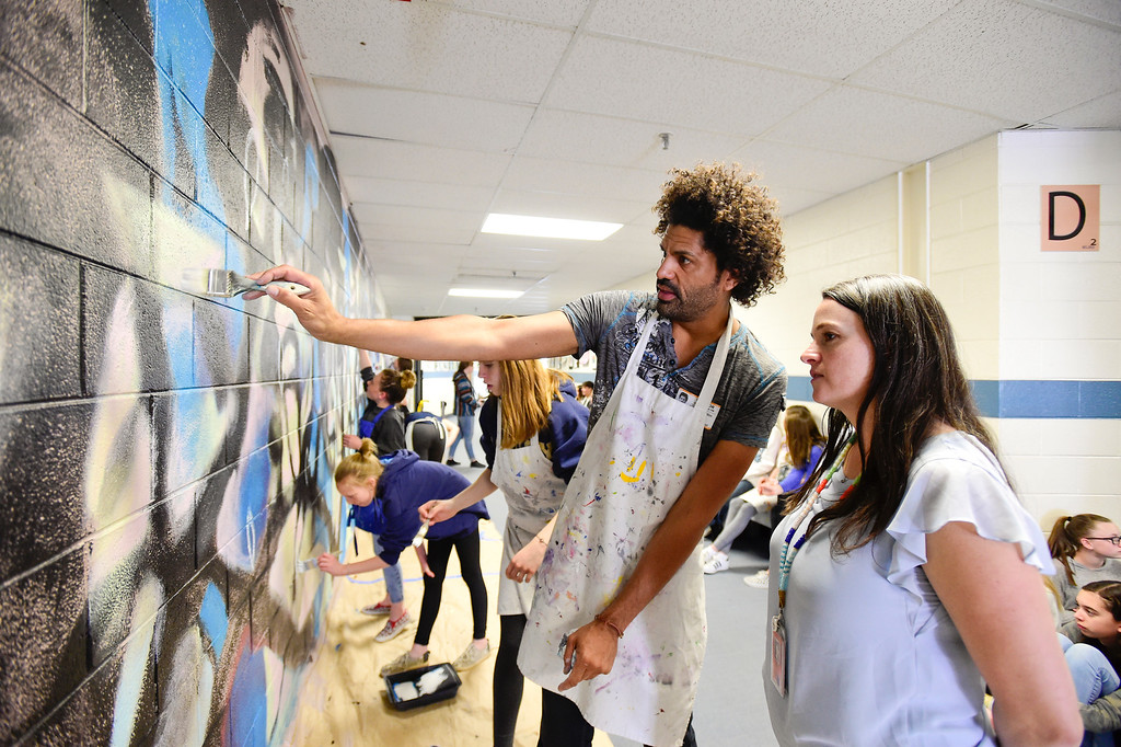 . BROOMFIELD, CO - APRIL 8:Artist Michael Gadlin, left, talks with Principal Dr. Rachel Heide, right, while working with students on a mural at Westlake Middle School in Broomfield on April 8, 2019. Gadlin is working with students to paint a 34-foot-long mural inside the school. (Photo by Matthew Jonas/Staff Photographer)