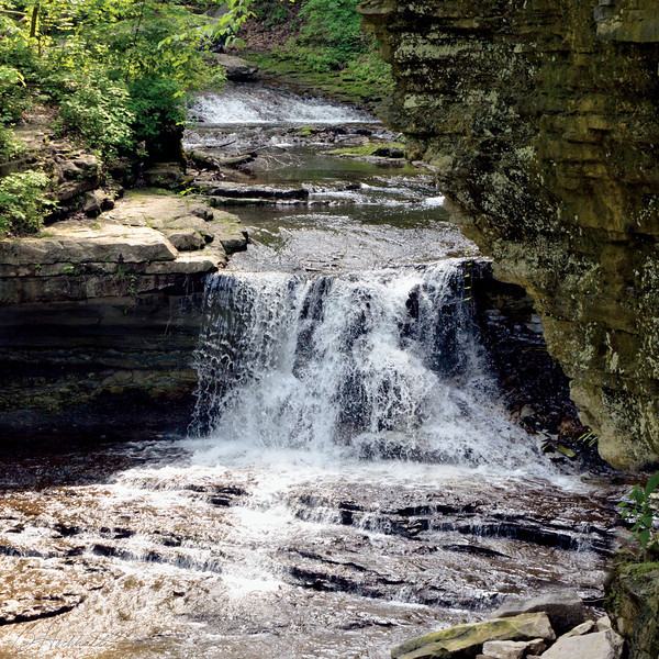 McCORMICK'S CREEK FALLS - McCormick's Creek State Park, Indiana<br /> <br /> With more than 10 miles of hiking trails, ranging in difficulty from easy to rugged, and an accessible trail at the park's nature center, McCormick's Creek State Park is a paradise for explorers of all abilities.<br /> <br /> Located near Spencer, the park boasts a spectacular limestone canyon, flowing creek, and scenic waterfalls.   The canyon's upper levels are around 700 feet above sea levels, dropping to the West Fork of the White River which is near 540 feet above sea level.<br /> <br /> Opened in 1916, Indiana's first state park also contains its share of historical attractions. The Statehouse Quarry near White River furnished limestone used for the Indianapolis Statehouse.  The stone arch bridge was built by the Civilian Conservation Corps in the 1930s, and both it and the gatehouse are listed in the National Register of Historic Places.<br /> <br /> Hiking trails at McCormick's Creek wind through creek beds and canyons, as well as a diverse mix of trees, spicebush, and native wildflowers.  At the end of the day, park visitors can relax at The Canyon Inn, a 70-room historic lodging facility complete with a restaurant, which is open year-round.