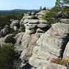 CAMEL ROCK AT GARDEN OF THE GODS - Shawnee National Forest, Illinois<br /> <br /> So named for the dromedary which it resembles, Camel Rock is seen at the end of the rock formation in this picture.  Other colorfully-named outcroppings at Garden of the Gods, part of Shawnee National Forest, include Mushroom Rock, Anvil Rock, and Monkey Face.<br /> <br /> The sandstone rock formations at Garden of the Gods are about 320 million years old. At one time, most of Illinois, western Indiana and western Kentucky were covered by a giant inland sea. As rivers carried sand and mud to the sea, layers of sediment formed which compressed over time into rock thousands of feet thick. At Garden of the Gods, they were about 4 miles deep. <br /> <br /> Shifts in the Earth's surface filled in the inland sea and fractured the bedrock, exposing it to wind, rain and freeze/thaw cycle.  Over time, these natural forces sculpted from the layers of sediment the beautiful formations known as Garden of the Gods.<br /> <br /> The Garden of the Gods Observation Trail is a quarter mile stone path which allows visitors easy access to some of the most spectacular views in Southern Illinois. An interpretive trail, educational markers provide information about the history and geology of the area.