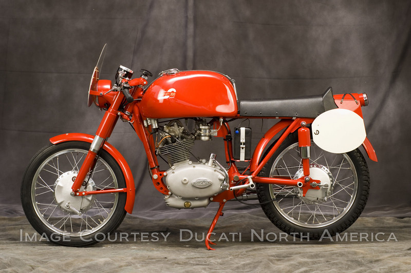 "1955 100 Gran Sport ""Marianna""<br /> OWNER - Jerry Dean<br /> Condition - Restored<br /> The first Ducati designed by Fabio Taglioni. Built in limited numbers for racing it was highly successful. This bike is displayed in street trim."