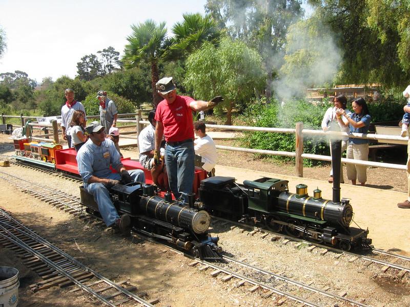 Steve Kramer (seated on locomotive), Dan O'Brien (red T-shirt, pointing).