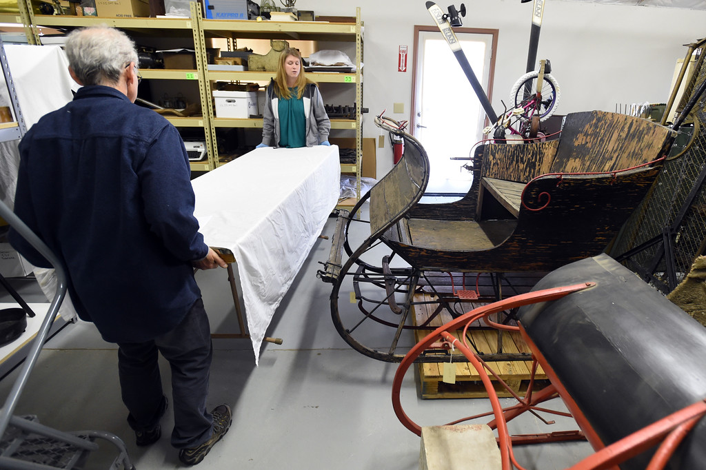 . Kristin Lewis and Tim Imbrock, move a table past  two old sleighs in the storage area. The new Museum of Boulder, opening next year, has announced its permanent exhibits and the crew over at its Gunbarrel artifacts facility were cataloguing and preparing the artifacts for the exhibits. Cliff Grassmick  Staff Photographer April 5, 2017
