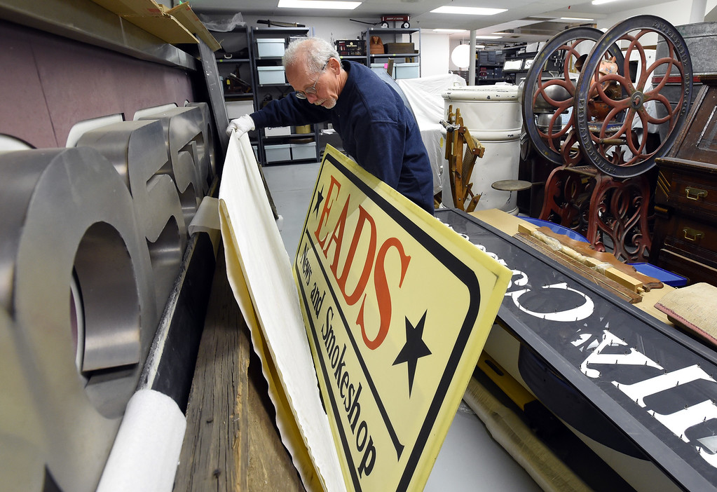 . Tim Imbrock moves the Eads News and Smokeshop sign stored at the facility. The new Museum of Boulder, opening next year, has announced its permanent exhibits and the crew over at its Gunbarrel artifacts facility were cataloguing and preparing the artifacts for the exhibits. Cliff Grassmick  Staff Photographer April 5, 2017