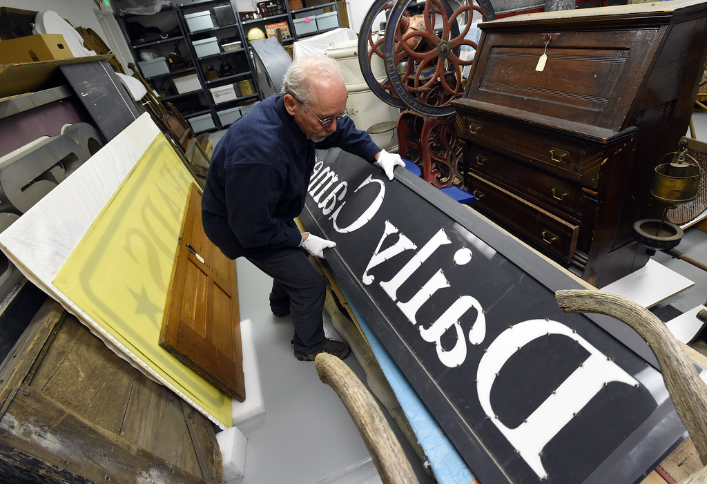 ". Tim Imbrock moves a ""Daily Camera\"" sign stored at the facility. The new Museum of Boulder, opening next year, has announced its permanent exhibits and the crew over at its Gunbarrel artifacts facility were cataloguing and preparing the artifacts for the exhibits. Cliff Grassmick  Staff Photographer April 5, 2017"