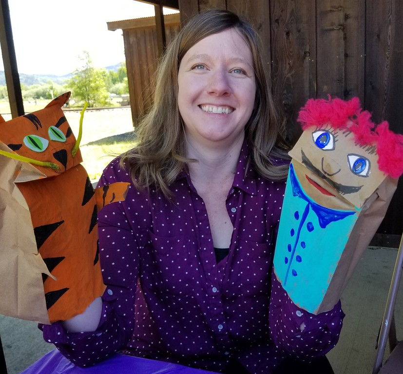 . Aura Whittaker for the Willits News Museum curator Karen Mattsen shows off the paper bag puppets she said she was inspired to make based off some of the art pieces in the new exhibit.