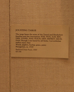 "At the Metropolitan Museum of Art. ""Jousting targe The target bears the arms of the Tansel and Rindscheit families and the inscription WIE WOL ICH BIN DER VOGEL HAS NOCH DEN ERFRET MICH DAS; Though I am hated by all birds, I nevertheless rather enjoy that. Wood, pigskin, burlap, gesso, paint. Hungarian, ca 1500"""