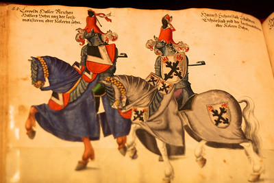 "At the Metropolitan Museum of Art. ""Tournament book Pen and colored wash on paper German (Nuremberg) late 16th century This book records a series of jousts held in Nuremberg between 1446 and 1561.  The participants, whose names are written above the figures, are armed for the Gestech, the joust fought with blunt lances.  A helm and a four pronged lance head similar to those illustrated in this book are exhibited at the left.  Books such as these provide an invaluable record of the colorful costumes, fanciful crests, and humorous, often satirical emblems that embellished the jousters' shields and horse trappings."""