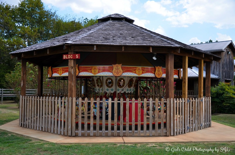"""September 25, 2015<br /> <br /> """"CHILDREN'S CAROUSEL"""" (Building #5)<br /> <br /> """"Life is like a carousel. Sometimes, you're up. Sometimes, you just go around. Sometimes, you're proud. Remember to enjoy the ride."""" ~ Author Unknown <br /> <br /> Did you know that the first carousel to be seen in the United States was created in Hessville, Ohio, approximately 25 miles from Toledo, Ohio on U.S. Route 20 during the 1840s by Franz Wiesenhoffer?<br /> <br /> The """"Children's Carousel"""" is in great shape - and not one rider. I aimed my camera over the wooden picket fence to capture this photo. On the day of our visit, my guest and I practically had the place all to ourselves. It was a beautiful day and the weather was perfect!<br /> <br /> """"Our classic American carousel, manufactured by the Allan-Herschell Company of North Tonawanda, New York, in 1928, has been located at the Mississippi Agriculture and Forestry Museum since 1988. The carousel was fully restored in 2013, made possible by North American Midway Entertainment. Children under the age of 5 can ride the carousel. The carousel is available Monday – Saturday, 9am-3pm. The cost is $1 per rider."""" ~ Reprinted text from here:<br /> <br /> <a href=""""http://www.mdac.state.ms.us/agmuseum/train-and-carousel-rides.htm"""">http://www.mdac.state.ms.us/agmuseum/train-and-carousel-rides.htm</a><br /> <br /> A photo of the carousel enclosed in the wooden picket fence is here:<br /> <br /> <a href=""""https://godschild.smugmug.com/Museums/Mississippi-Forestry-and/i-hbH3Bq2/A"""">https://godschild.smugmug.com/Museums/Mississippi-Forestry-and/i-hbH3Bq2/A</a><br /> <br /> MS Forestry and Agriculture Museum/National Agricultural Aviation Museum<br /> 1150 Lakeland Drive<br /> Jackson, MS<br /> Official website: <a href=""""http://www.mdac.state.ms.us/agmuseum/index.html"""">http://www.mdac.state.ms.us/agmuseum/index.html</a><br /> <br /> My Homepage:  <a href=""""http://www.GodsChild.SmugMug.com"""">http://www.GodsChild.SmugMug.com</a>"""