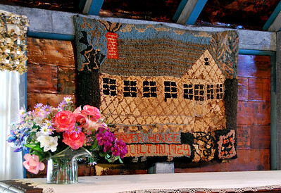 A needlepoint rendition of the Paper House.