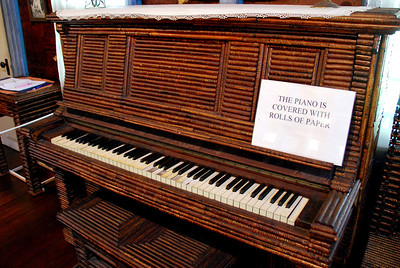 Rolls of newspaper cover the piano.
