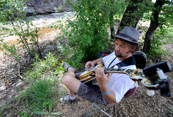 "Russell Bloom of Littleton gets some quiet time by the water during the instruction week at Rocky Grass.<br /> Over 300 students are learning from the bluegrass masters during the 2011 Rocky Grass Academy in Lyons this week.<br /> For more photos and a video of the academy, go to  <a href=""http://www.dailycamera.com"">http://www.dailycamera.com</a>.<br /> Cliff Grassmick / July 26, 2011"