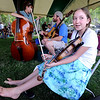 "Rosalee Walsh, 11,  of Ridgeway, takes time to stretch her legs after playing the fiddle.<br /> Over 300 students are learning from the bluegrass masters during the 2011 Rocky Grass Academy in Lyons this week.<br /> For more photos and a video of the academy, go to  <a href=""http://www.dailycamera.com"">http://www.dailycamera.com</a>.<br /> Cliff Grassmick / July 26, 2011"